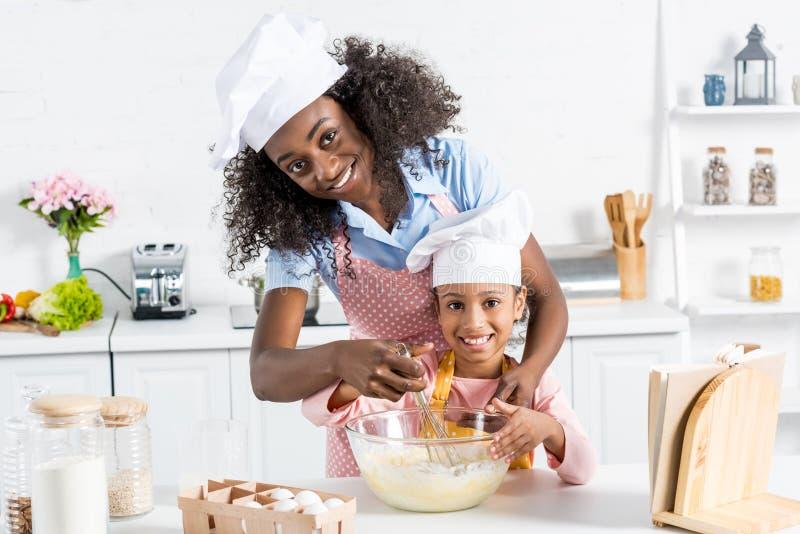 de Afrikaanse Amerikaanse moeder en dochter die in chef-kokhoeden deeg de mengen met zwaaien stock foto's