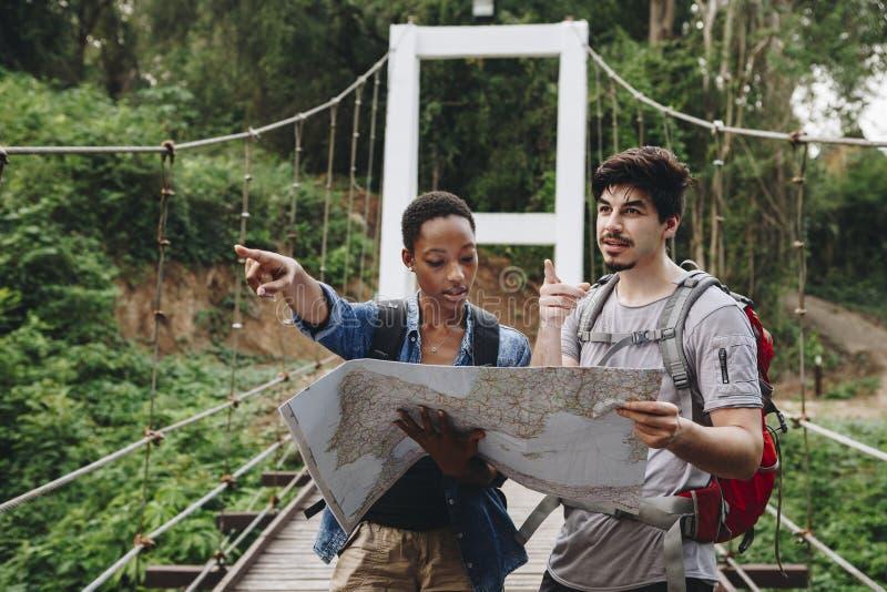 De Afrikaanse Amerikaanse vrouw en een Kaukasische man die een kaart reizen samen en groepswerkconcept bekijken stock fotografie