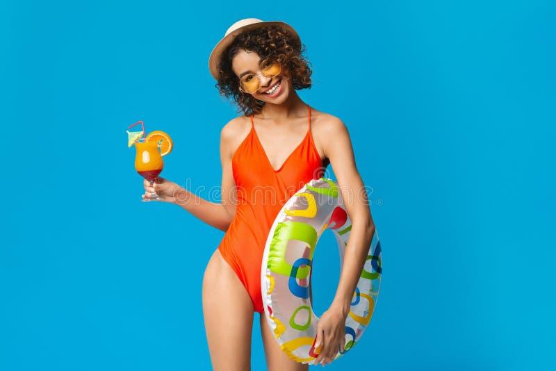 De Afrikaanse Amerikaanse vrouw met de zomercocktail en zwemt ring stock foto