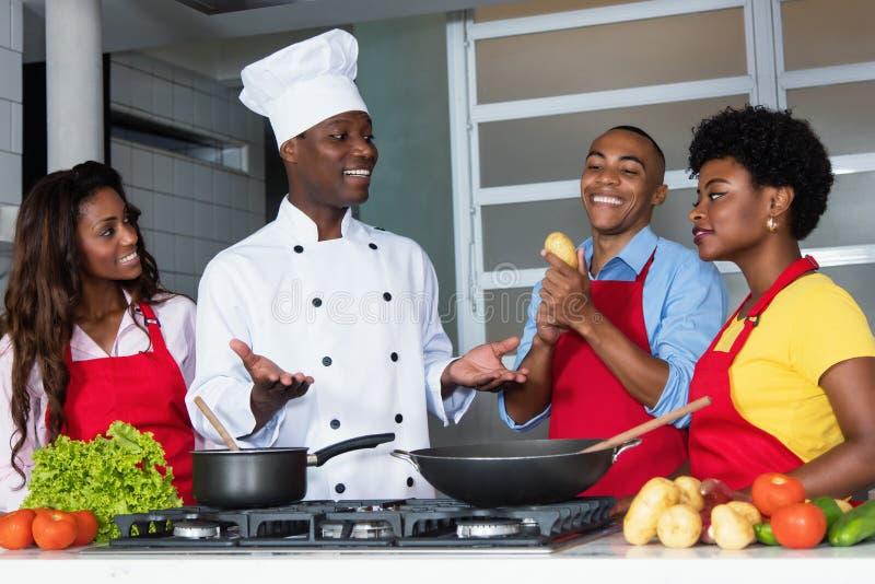 De Afrikaanse Amerikaanse vrouwen en de mannen van het chef-kokonderwijs bij keuken stock afbeelding