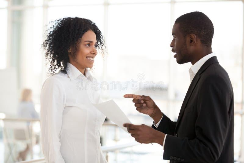 De Afrikaanse Amerikaanse zakenman bevordert opgewekte vrouwelijke vergadering in h stock foto's