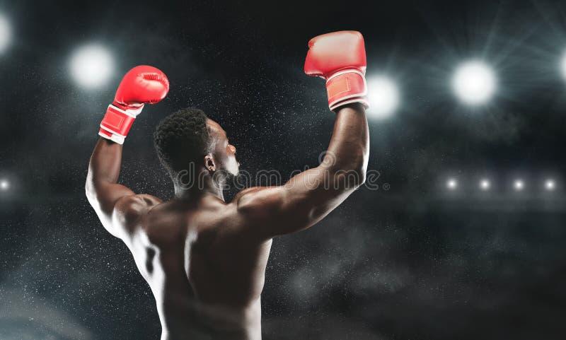 De Afrikaanse bokser die van hem opheffen dient bokshandschoenen aan publiek in bij stadion royalty-vrije stock afbeelding