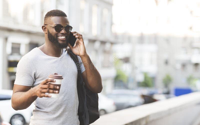 De Afrikaanse mens met koffie om te gaan heeft plezierig gesprek stock fotografie