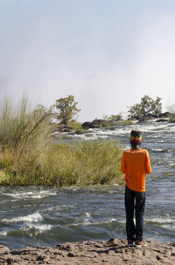De Afrikaanse mens met traditionele kleurrijke slijtage aan Zambezi rivierkant bovenop Victoria valt, Livingstone, Zambia stock foto's