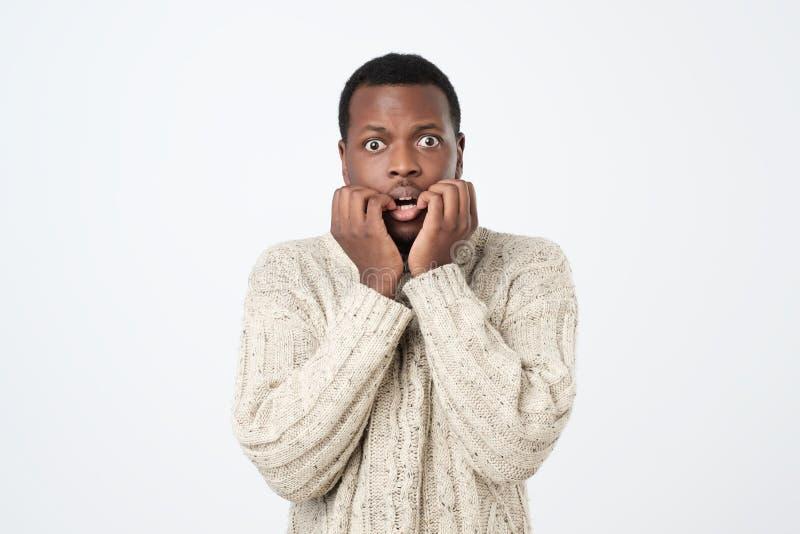 De Afrikaanse mens met zenuwachtige uitdrukking, de spijkers van de betenvinger, maakt zich vóór gesprek ongerust stock foto