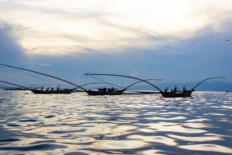 De Afrikaanse Mensen die van het oosten op een Meer met de Bezinning van de Zon over Water vissen royalty-vrije stock afbeelding