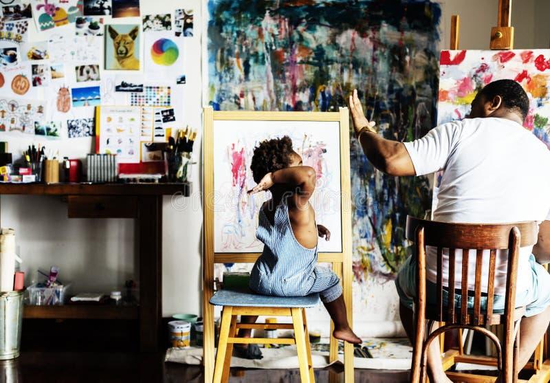 De Afrikaanse papa die van de afdalingskunstenaar zijn kind een hoogte vijf geven royalty-vrije stock afbeeldingen