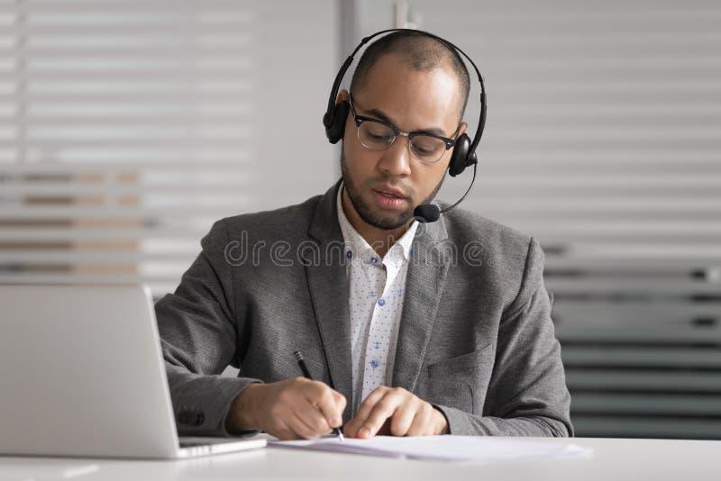 De Afrikaanse de slijtagehoofdtelefoon van de klantenondersteuningsagent schrijft de nota's videovraag maken stock afbeeldingen
