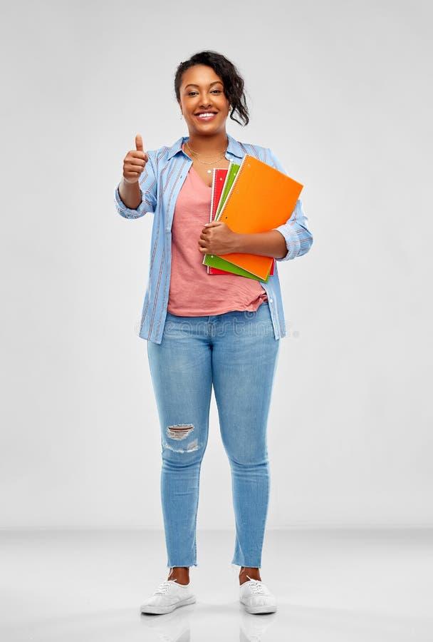 De Afrikaanse student met notitieboekjes het tonen beduimelt omhoog stock afbeelding