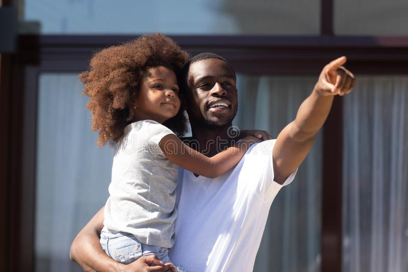 De Afrikaanse vader houdt dochter op handen die iets het interesseren tonen stock foto's