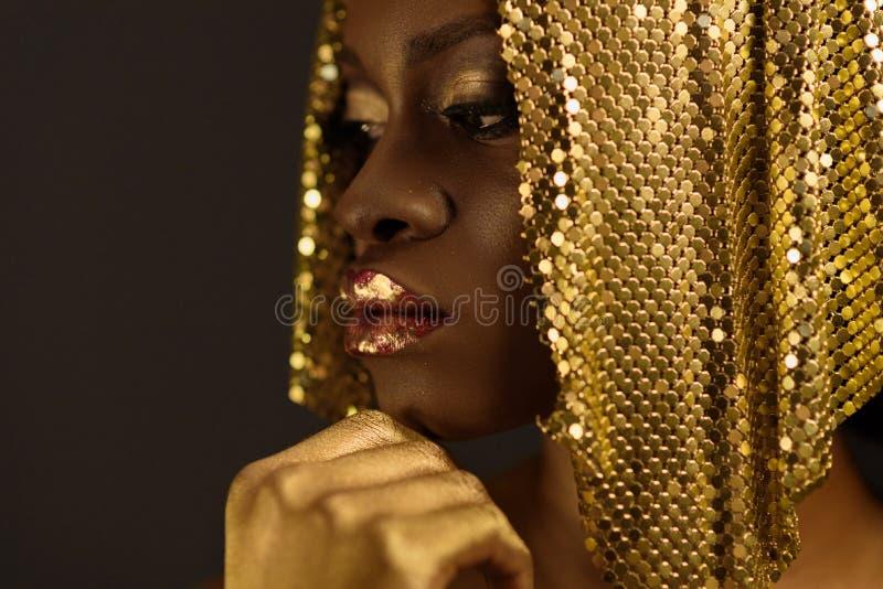 De Afrikaanse vrouw die met gouden metaalsamenstelling en volledige glanzende lippen weg houdend kin, sluit omhoog kijken stock afbeeldingen