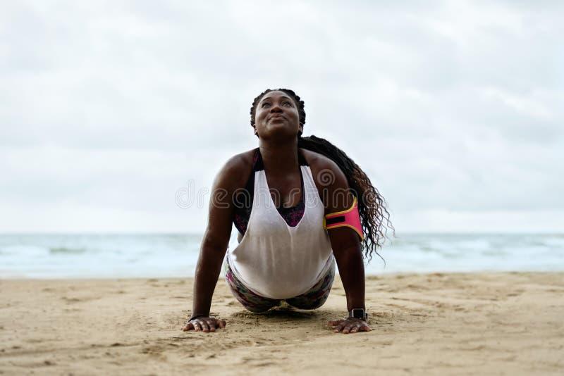 De Afrikaanse vrouw die van de opdrukoefeningengeschiktheid opdrukoefeningen buiten op strand doen stock foto