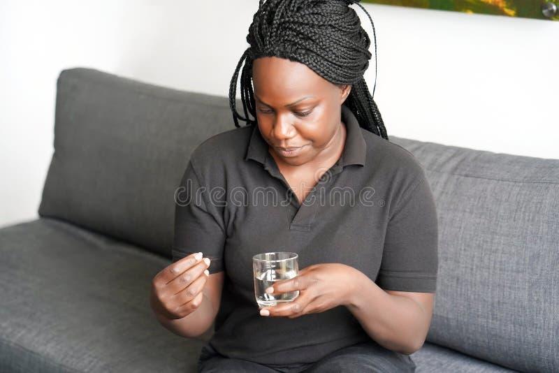 De Afrikaanse vrouw drinkt een pil van pijn royalty-vrije stock afbeeldingen