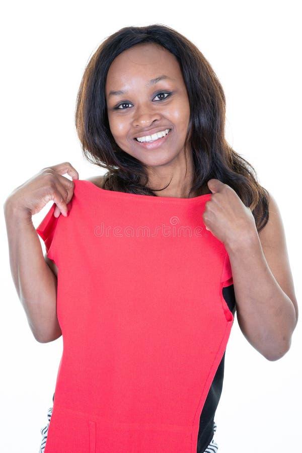 De Afrikaanse vrouw in een rode kleding kijkt in de spiegel en kiest de kleren gelukkig glimlachen stock foto