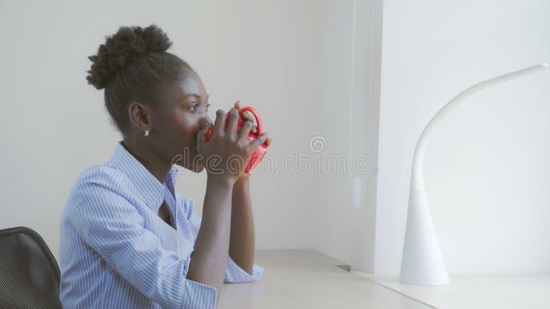 De Afrikaanse vrouwelijke droom en drinkt thee royalty-vrije stock foto