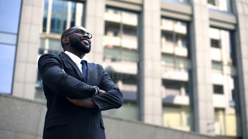 De Afro-Amerikaanse mens in kostuum kijkt omhoog in rooskleurige die toekomst, voor succes wordt gemotiveerd royalty-vrije stock foto's