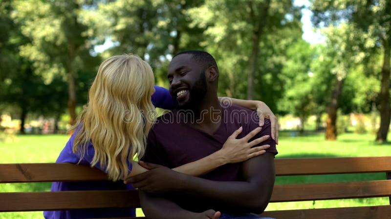 De Afro-Amerikaanse mens omhelst van erachter, en vrouw die, verrassing lacht glimlacht stock afbeeldingen