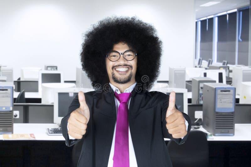 De Afrozakenman toont duimen in de werkplaats royalty-vrije stock afbeelding