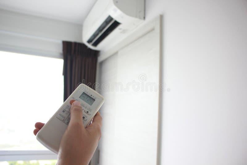 De afstandsbediening van de handgreep op de airconditioner wordt geleid die stock afbeeldingen