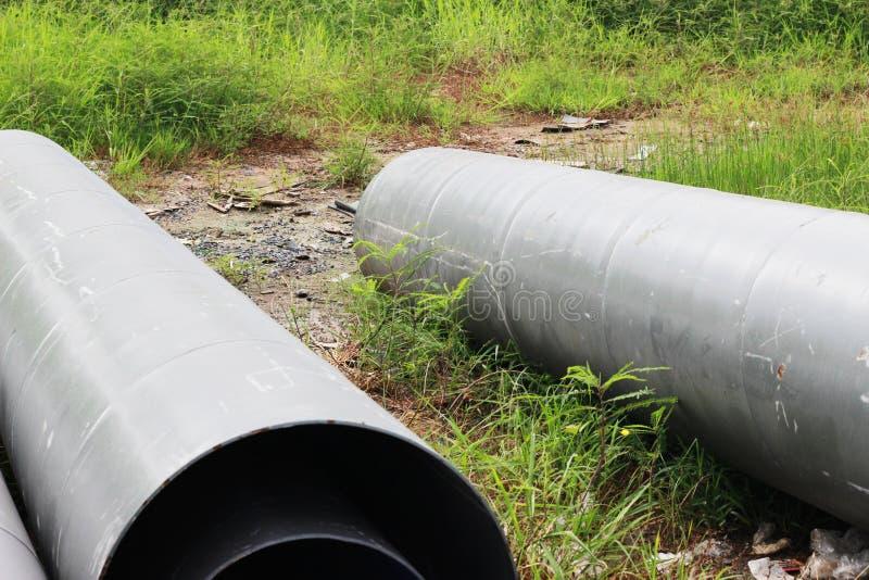 De afvoerkanalen worden in openlucht geplaatst, wachtend op bouw, met onkruid stock afbeelding