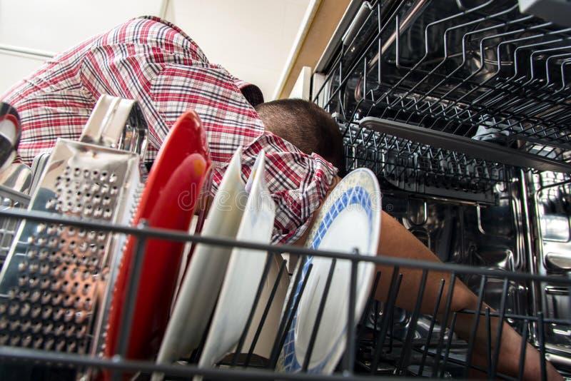 De afwasmachine van de manusje van allesreparatie in de keuken stock foto's