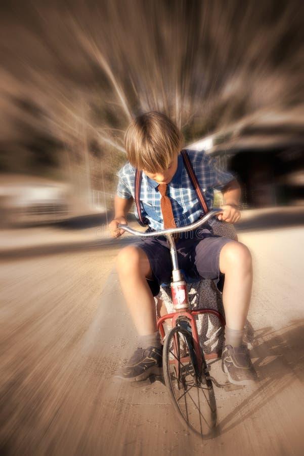 De afwijkingsjongen van de tijd op fiets stock foto
