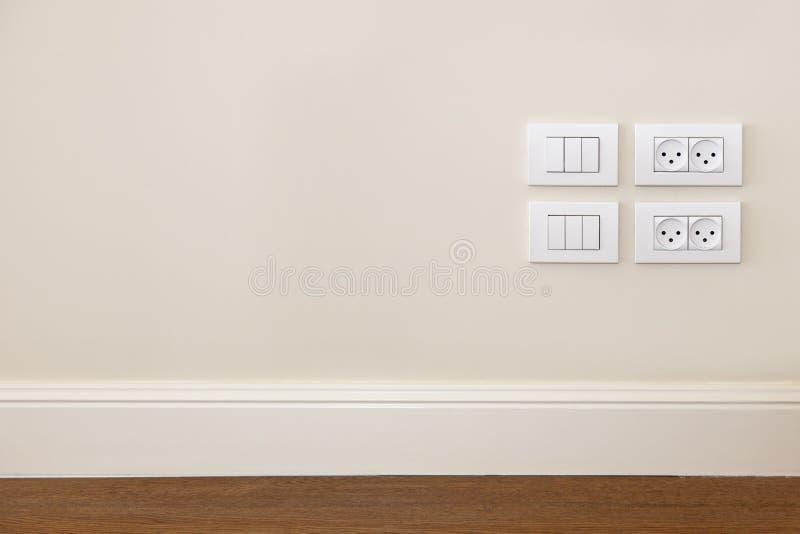 De afzet van de macht en het licht schakelen de muur in stock fotografie