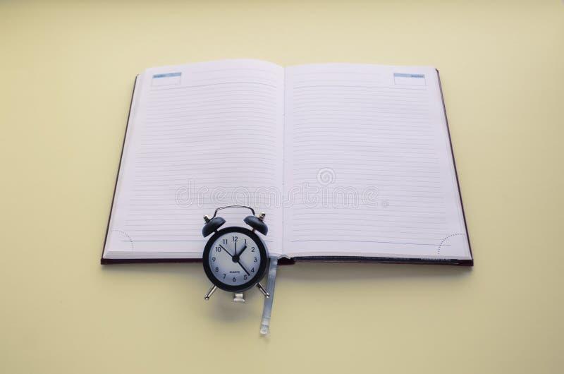 De agenda en de klok, op tijd, om aan de kalender en de agenda te schrijven De ruimte van het exemplaar royalty-vrije stock foto