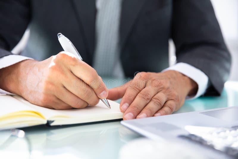De Agenda van zakenmanwriting schedule in stock afbeeldingen