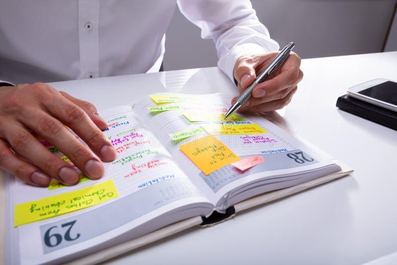 De Agenda van zakenmanwriting schedule in stock fotografie