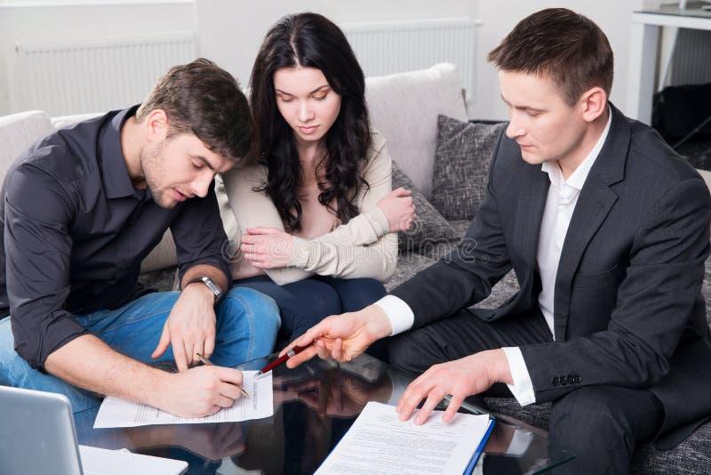 De agent adviseert het paar, die documenten ondertekenen royalty-vrije stock fotografie