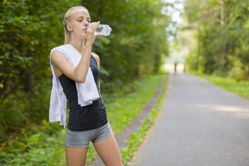 De agent drinkwater van de vrouw na het lopen stock afbeeldingen