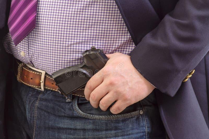 De agent van de close-upveiligheid in pak met handkanon in bijlage op riem Op wit royalty-vrije stock foto