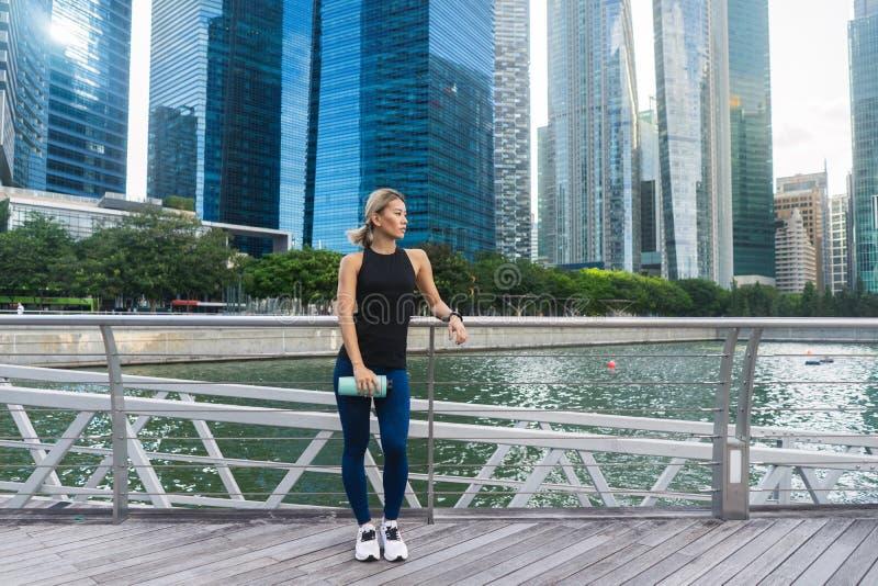 De agent van de geschiktheids het Aziatische vrouw ontspannen na stad het lopen stock fotografie