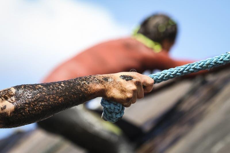 De agenten van het modderras, die hindernissen verslaan door kabel te gebruiken stock afbeelding