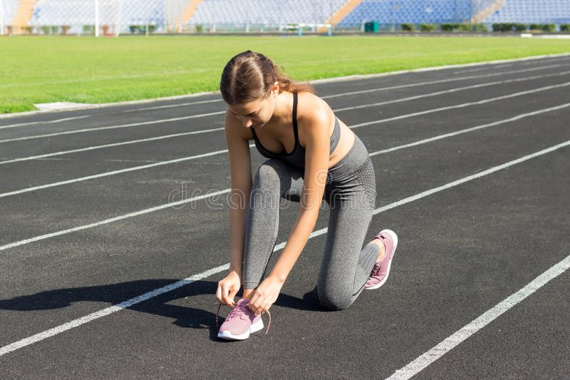 De agentvrouwen die schoenen binden rijgt klaar het worden voor ras op looppasspoor in stadionsport en fitness concept stock afbeelding