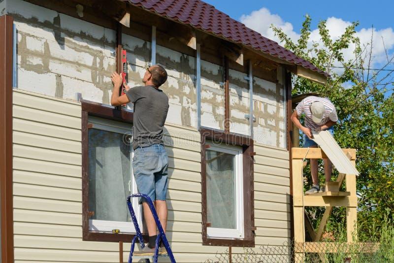 6 de agosto de 2017: La foto de dos trabajadores cubre la fachada fotografía de archivo libre de regalías