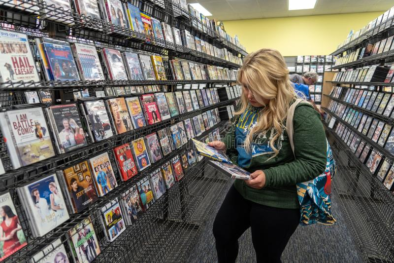 12 DE AGOSTO DE 2018 - FAIRBANKS, AK: La mujer rubia hace compras para los alquileres de la película en una tienda video de la su imagenes de archivo