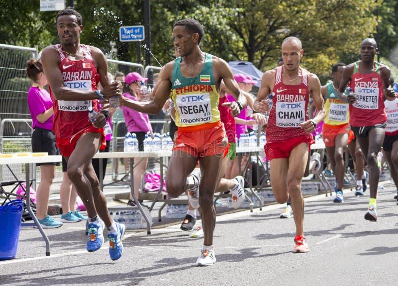 6 de agosto ` 17 - maratona dos campeonatos do atletismo do mundo de Londres: Bahrainian DECHASA passa a garrafa de água a TSEGAY fotos de stock