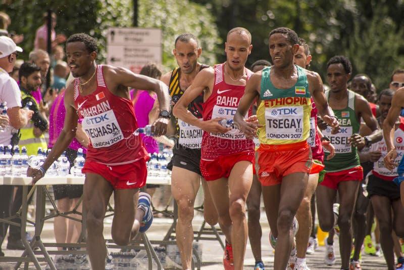 6 de agosto ` 17 - maratona dos campeonatos do atletismo do mundo de Londres: Bahrainian DECHASA passa a garrafa de água a TSEGAY fotos de stock royalty free