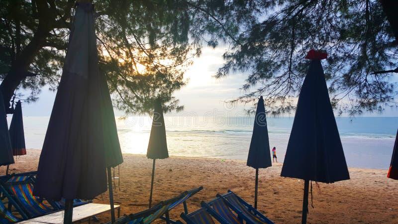 3 DE AGOSTO DE 2018: Mostre em silhueta a cadeira de praia e o guarda-chuva na praia da manhã, fundo bonito da opinião do mar em  fotos de stock royalty free