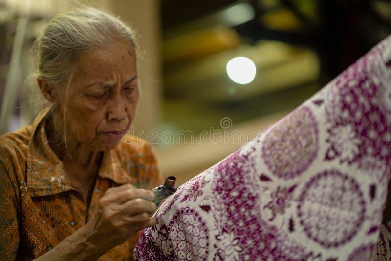 11 de agosto de 2019, Surakarta Indonésia: Mulher que faz o Batik com mão ascendente próxima para fazer o batik na tela usando a  fotos de stock
