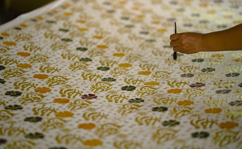 11 de agosto de 2019, Surakarta Indonesia: Mano ascendente cercana para hacer el batik en la tela con el biselaje con el fondo de foto de archivo libre de regalías