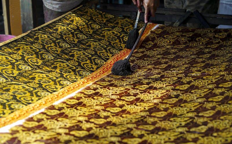 11 de agosto de 2019, Surakarta Indonesia: Mano ascendente cercana para hacer el batik en la tela con el biselaje con el fondo de fotos de archivo