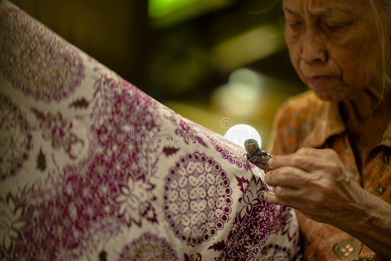 11 de agosto de 2019, Surakarta Indonesia: Mujer que hace el batik con la mano ascendente cercana para hacer el batik en la tela  fotografía de archivo