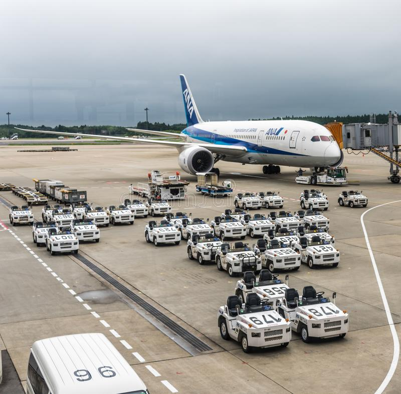 18 de agosto de 2017: Tractores de la Cargo-carga del aeropuerto internacional de Narita, de Tokio, de Japón y todo el avión de l fotografía de archivo