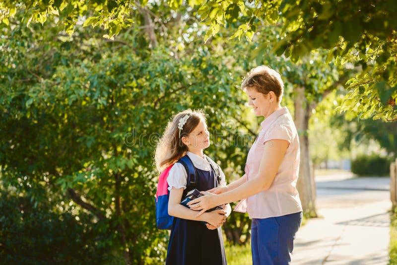 De Ahappymoeder begeleidt haar dochter aan school stock fotografie