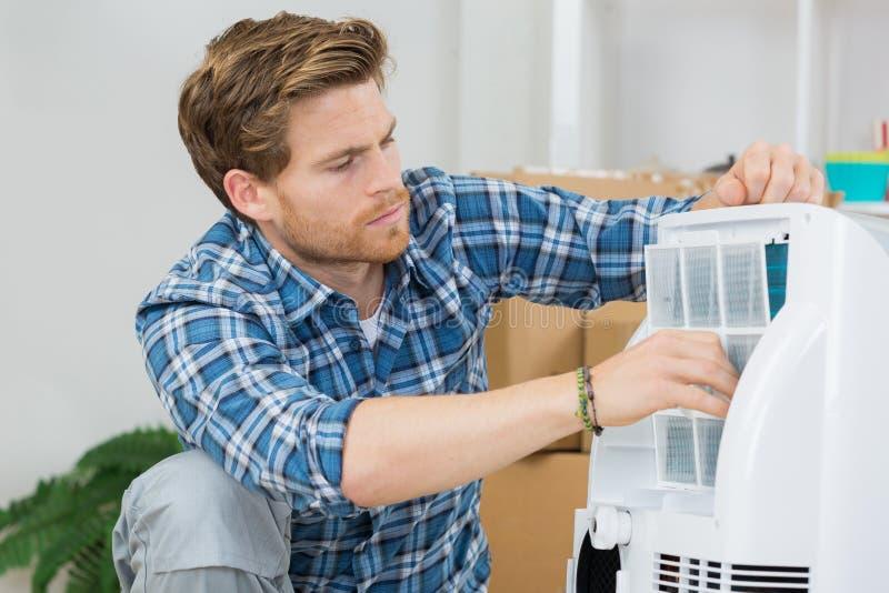 De airconditioningseenheid van technicusreparaties royalty-vrije stock afbeelding