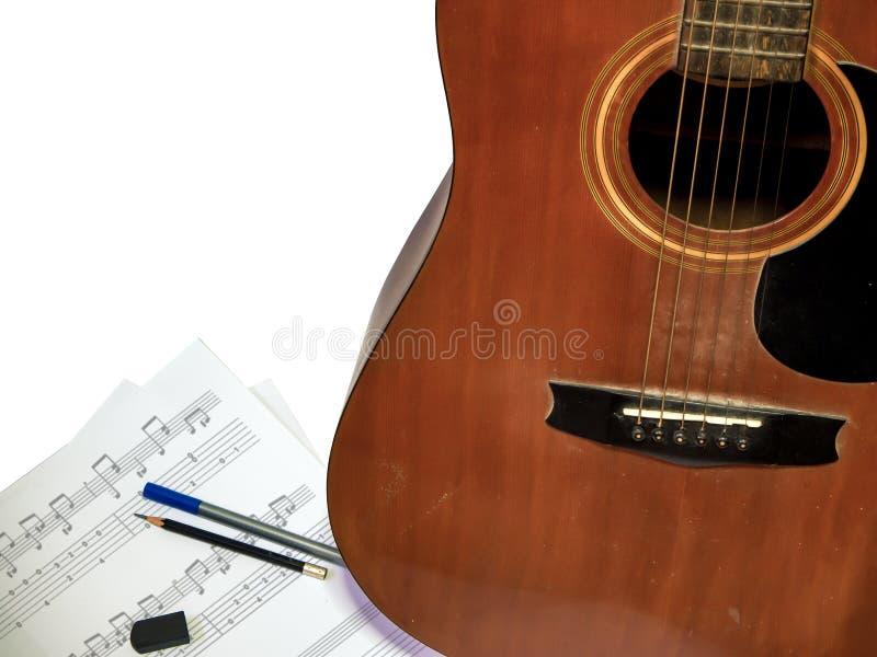 De akoestische gitaar wordt gebruikt samenstellend notalied met de geïsoleerde witte achtergrond van het penpotlood rubber royalty-vrije stock foto