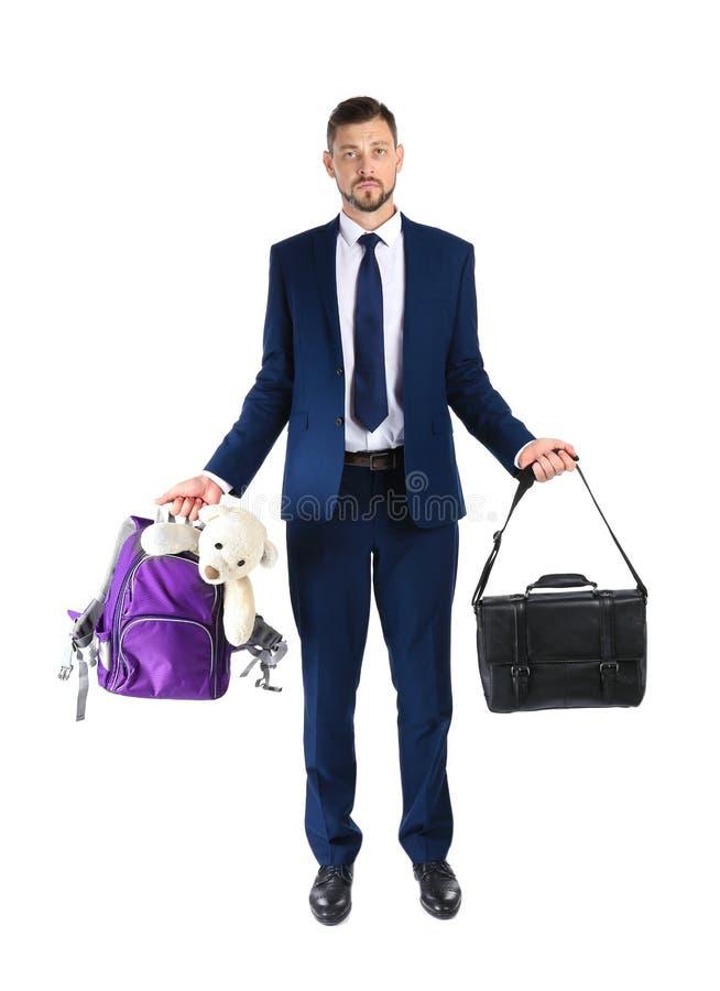 De aktentas en de rugzak van de zakenmanholding met stuk speelgoed op witte achtergrond stock fotografie